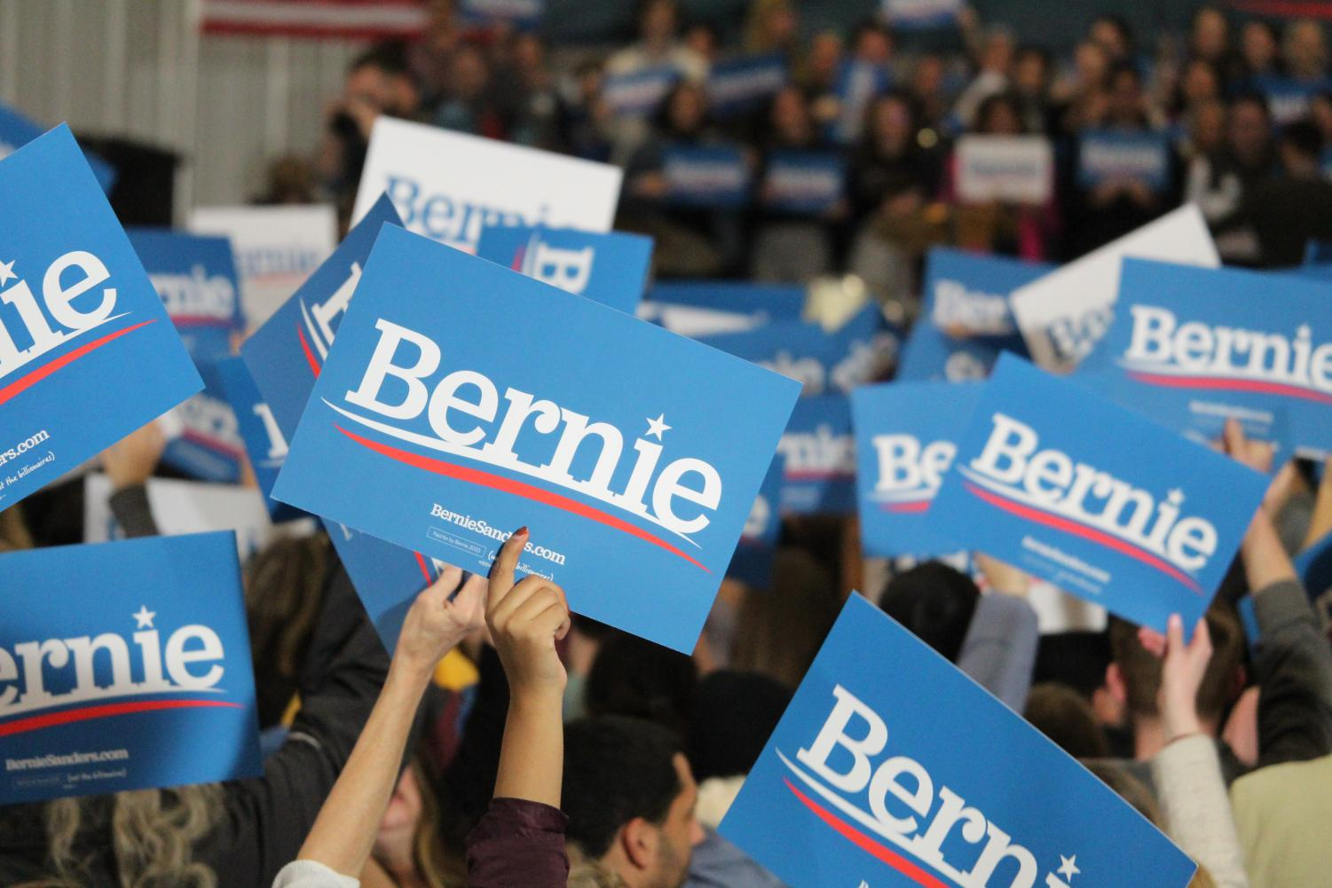 Campaign signs being held up at the Bernie Sanders rally in Council Bluffs at Iowa Western Community College on November 8, 2019.