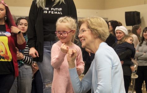 Democratic Presidential hopeful Senator Elizabeth Warren makes a promise with a young  girl after speaking at Wilson Middle School  on December 29, 2019.
