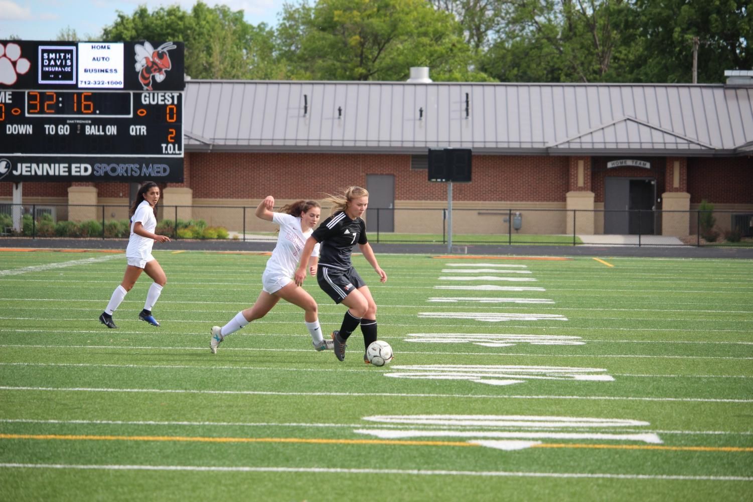 Allison Schubert keeping the ball away from one of the Bishop Heelan girls.
