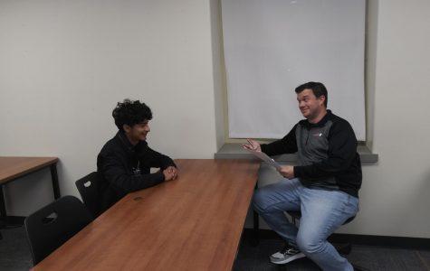 Mr. Renshaw, TJ's D.E.C.A. teacher, and Juan Carlos Martinez, a T.J. 12th grader, conduct a mock interview.