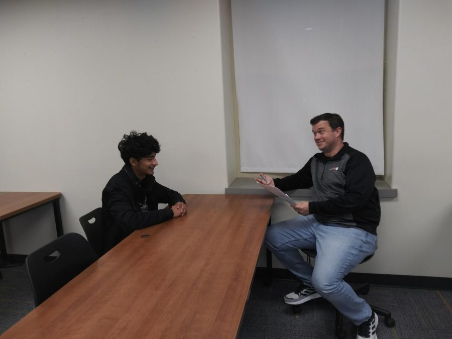 Mr. Renshaw, TJ's D.E.C.A. teacher, and Juan Carlos Martinez, a T.J. 12th grader, conduct a mock interview.
