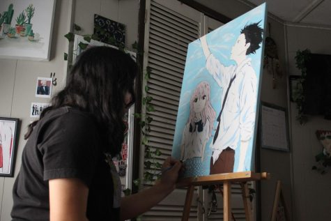 Sophomore, Leslie Hernandez, painting a piece of her artwork.